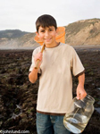 Picture of a young Hispanic or Mexican boy collecting specimens on the sea shore at low tide. The boy is carrying a large glass jar with some water in it and has an orange net over his shoulder.